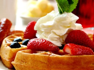 Top waffles with strawberries and whipped cream for a colorful presentation.  © istockphoto.com