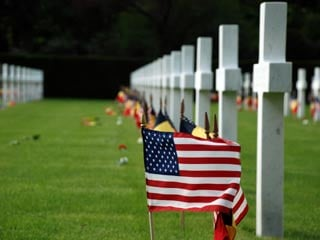 American and Belgian flags wave beside the tombstones of the 368 American World War I soldiers buried at Flanders Field in Belgium (©Armmry.mil/Bob McElroy)